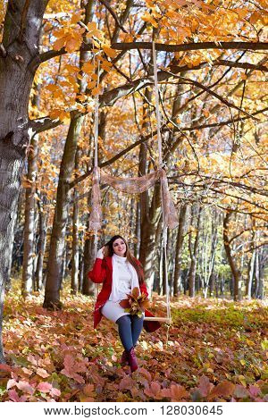 an expectant mother goes for a walk in the autumn park of swing bouquet