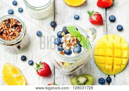 strawberry mango kiwi blueberry orange with Greek yogurt and granola in a jar