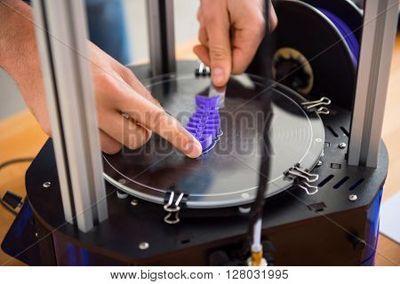 Be accurate. Close up of hands of pleasant person using  3d printer