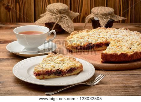 Cherry tart and cup of tea on wooden background.