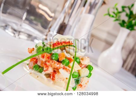 Salad Olivier with shrimps on white plate