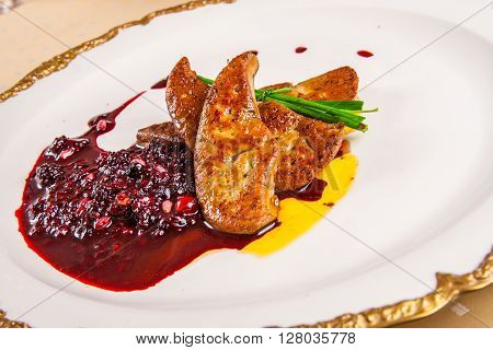 Foie gras with berries on white plate