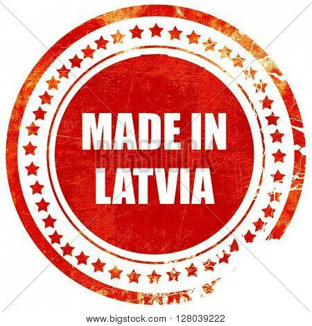 Made in latvia, grunge red rubber stamp on a solid white background