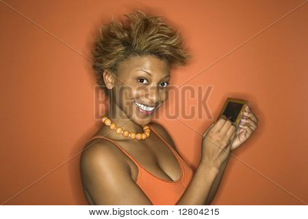 Portrait of smiling young African-American adult woman on orange background using her palmtop computer.