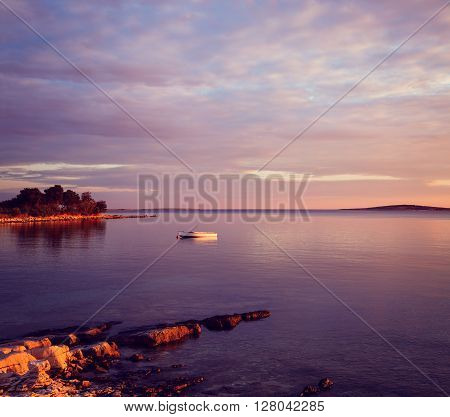 Beautiful Seascape with Lonely White Boat Floating in Sea at Sunset. Mediterranean Coastline in Croatia. Adriatic Sea. Peaceful Background with Tranquil Calm Water. Purple Toned Photo with Copy Space.