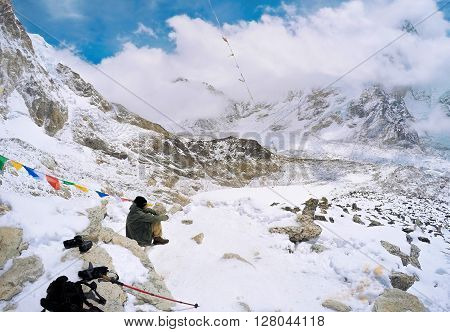 The asian photographer on the top of the mountain, Nature photographer with digital camera on top of the mountain, the photographer waiting good view of the mountain Everest, Himalaya mountain, Nepal
