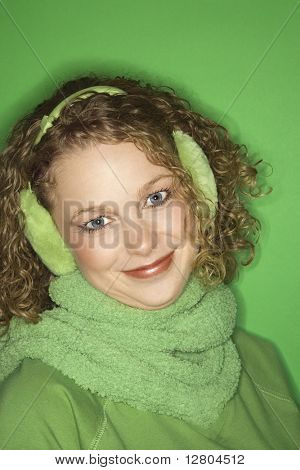 Portrait of smiling young adult Caucasian woman on green background wearing earmuffs, winter coat and scarf.