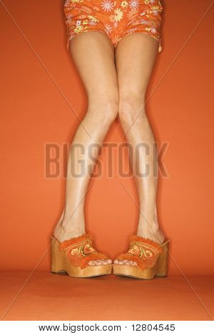 Legs and feet of Caucasian mid-adult woman standing pigeon-toed in chunky shoes on orange background.