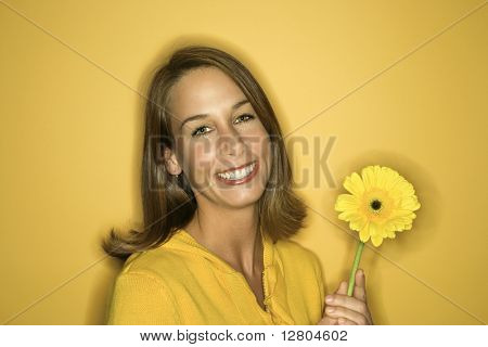 Portrait of smiling young adult Caucasian woman on yellow background holding flower.