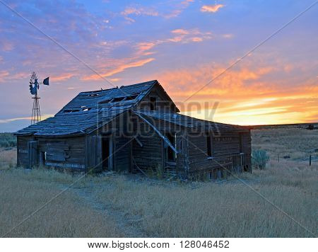 Old Homestead and windmill in centro Oregon at sunrise.
