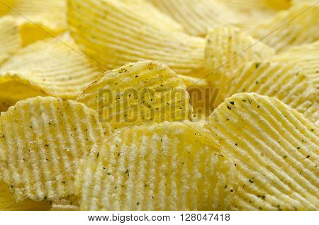 Potato chips striped with greens. Background of potato chips, close-up.