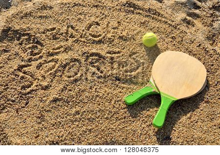 Pair of rackets and ball for sport on the beach with an inscription on the sand 'Beach Sports'
