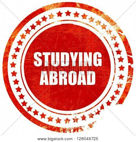 studying abroad, grunge red rubber stamp on a solid white background
