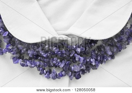 Strings of amethyst beads on white blouse closeup