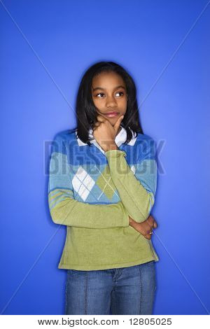 Portrait of African-American girl with hand on chin standing in front of blue background.