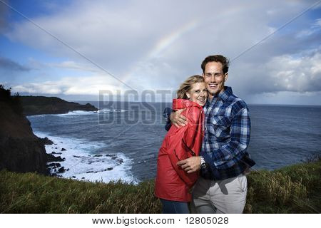 Caucasian mid-adult  couple embracing in front ocean with rainbow in background in Maui, Hawaii.