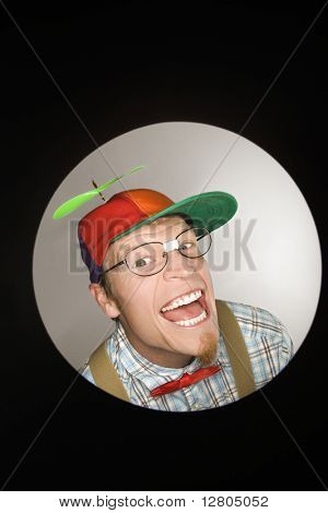 Close up circle vignette of Caucasian young man dressed like nerd wearing propeller cap with mischievous look.