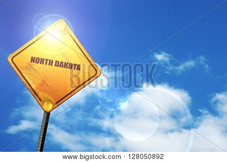 Yellow road sign with a blue sky and white clouds:  north dakota