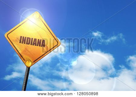 Yellow road sign with a blue sky and white clouds:  indiana