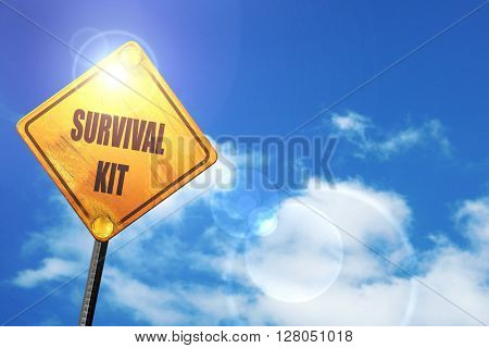 Yellow road sign with a blue sky and white clouds: Survival kit