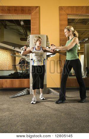 Prime adult Caucasian female helping mature adult Caucasian female use exercise equipment at gym.