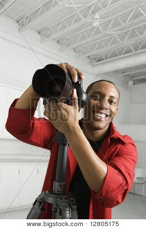 African American young male adult with camera on tripod looking at viewer smiling.