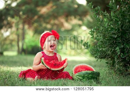 Laughing cute girl 1-2 year old eating water melon outdoors. Childhood. Healthy lifestyle.