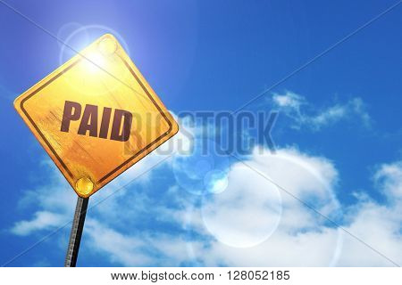 Yellow road sign with a blue sky and white clouds: paid sign bac