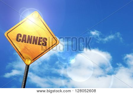 Yellow road sign with a blue sky and white clouds: Cannes