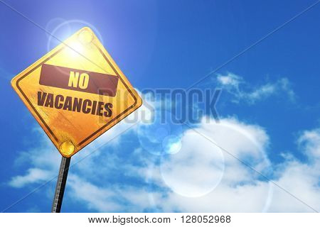 Yellow road sign with a blue sky and white clouds: Vacancy sign