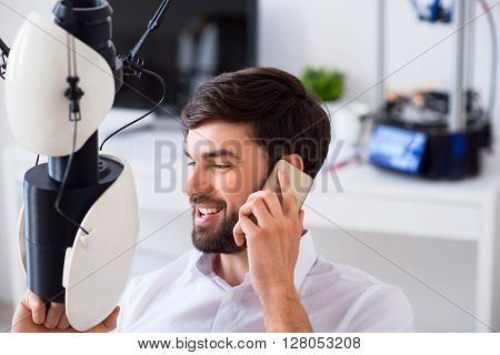 Share positivity.     Positive handsome man holding model printed on 3d printer and talking on cellphone while expressing gladness