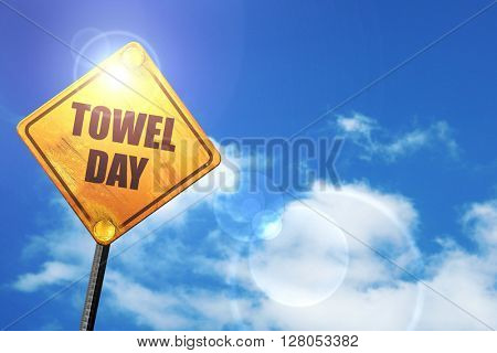 Yellow road sign with a blue sky and white clouds: towel day