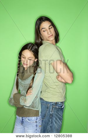 Portrait of Asian-American girl and teen boy standing back to back as boy looks down at girl over his shoulder.
