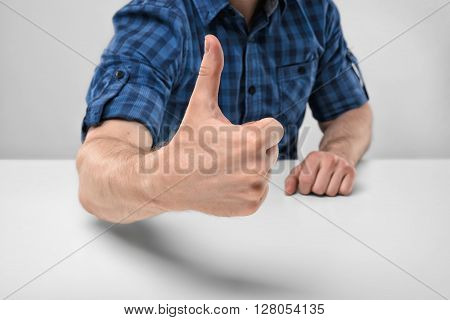 Cropped image of masculine hands showing thumbs up. Hand gesture. Good job. Symbols and gestures. Expression of approval. Successful outcome.