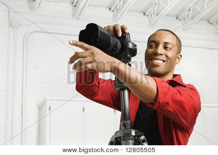 African American young male adult with camera and pointing.