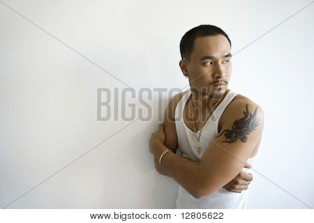 Portrait of Asian young adult man leaning against white wall with arms crossed looking over shoulder.