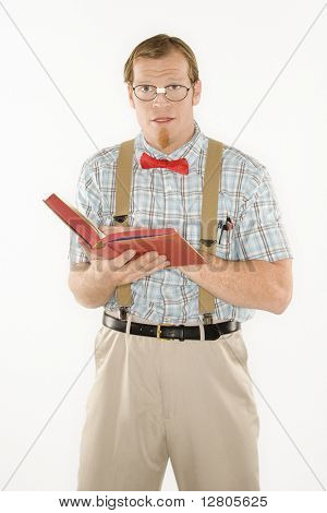 Caucasian young man dressed like nerd with book open looking at viewer.