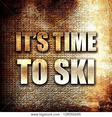 it's time to ski, written on vintage metal texture