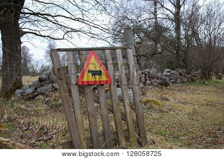 Rural landscape with a cattle warning sign on a small gate