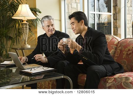 Prime adult Asian and Caucasian businessmen.