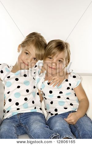 Female children Caucasian twins sitting together on chair.
