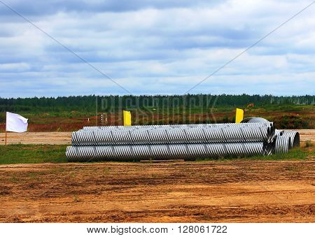 Corrugated aluminum rolls stacked at the site before construction