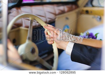 Women's and men's hand on steering wheel of a retro car. Bride in transparent gloves. Groom in a suit, white shirt and cuffs. A couple in a retro car.