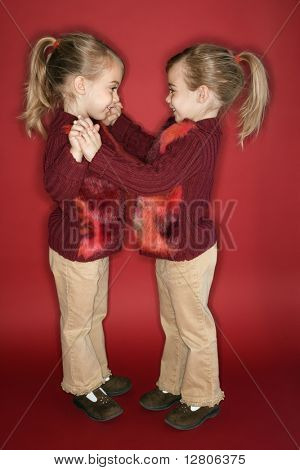 Female children Caucasian twins standing in dance stance.
