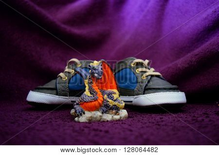 baby boy shoes with dragon fish bowl decoration on purple background