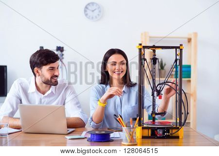 Nice device. Cheerful delighted smiling colleagues sitting at the table and   using 3d printer while expressing gladness
