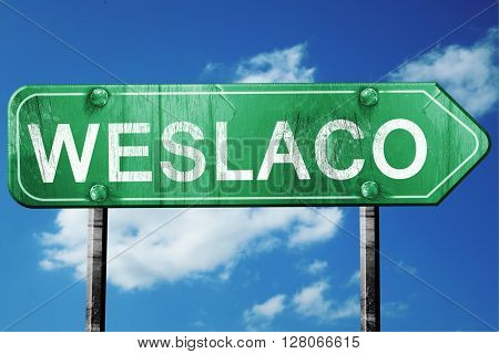 weslaco road sign , worn and damaged look