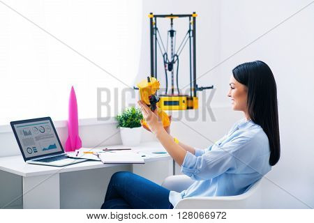 Magic invention. Pleasant beautiful smiling delighted woman sitting at the table and holding model printed on the 3dprinter while expressing gladness