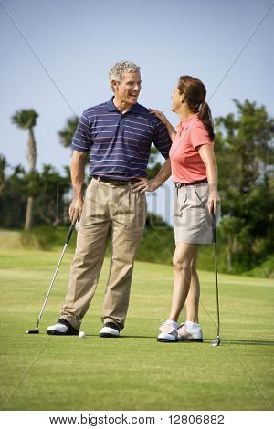 Caucasion mid-adult man and woman standing on golf course talking to each other.