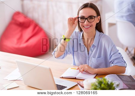 Like my work. Cheerful charming smiling girl holding her glasses and expressing gladness while sitting at the table